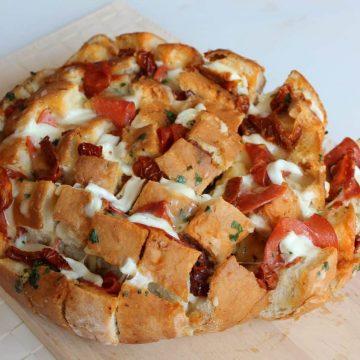 Stuffed pizza bread on a wooden chopping board.