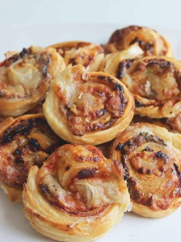 Bacon and cheese puff pastry pinwheels stacked on a white plate