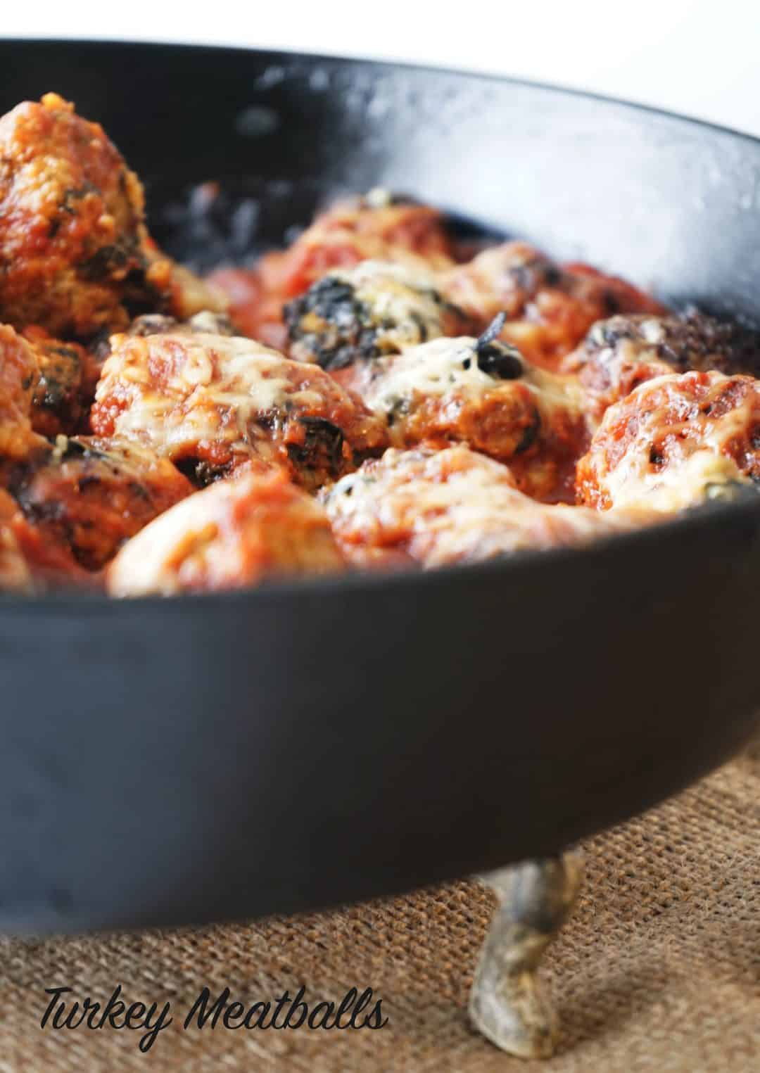 Turkey meatballs in a skillet in a marinara sauce and topped with cheese.
