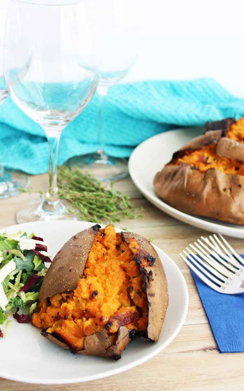 A twice baked stuffed sweet potato on a plate with salad