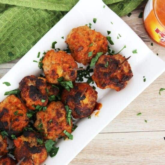 Top shot of baked pork meatballs on a white serving plate with a green cloth