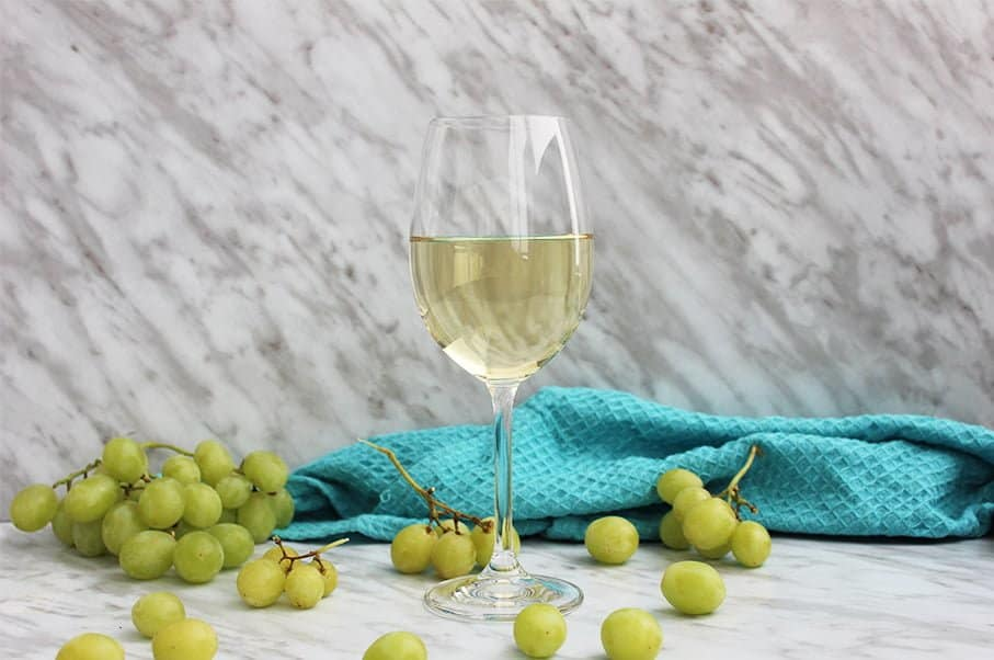 A glass of white wine with a blue cloth behind it