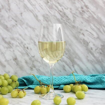 A glass of white wine on a marble background