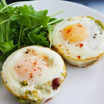 A closeup of two bacon and egg cups on a white plate