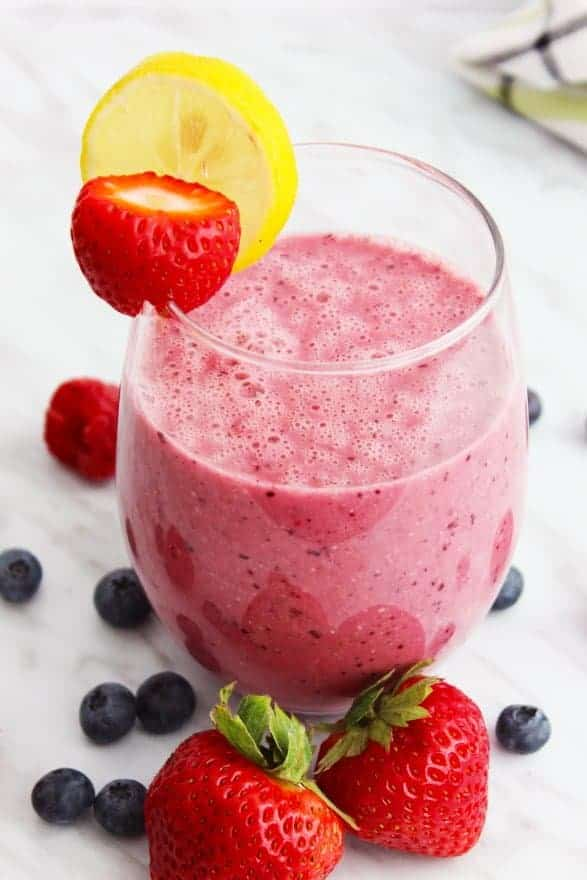 A berry oat smoothie garnished with a lemon slice and strawberry