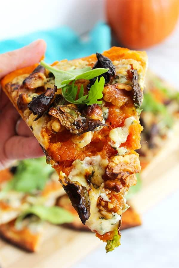 A slice of Blue Cheese Pizza with Pumpkin held towards the camera