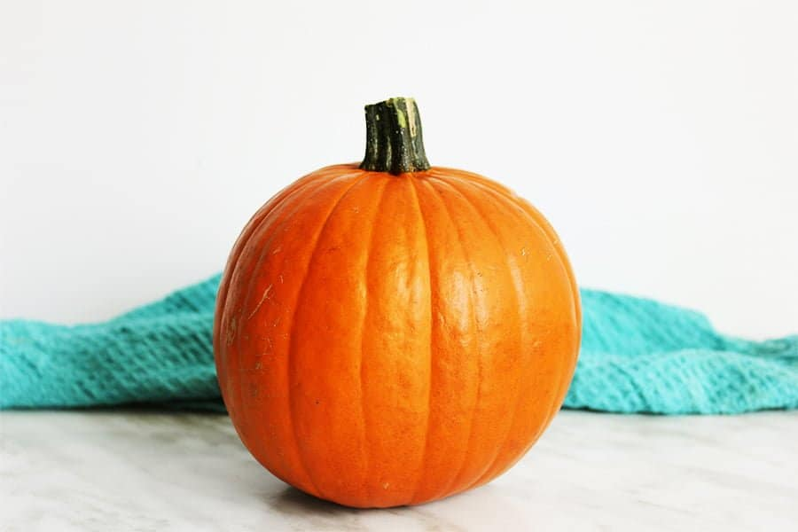 A whole pumpkin on a marble work top with a blue cloth behind it
