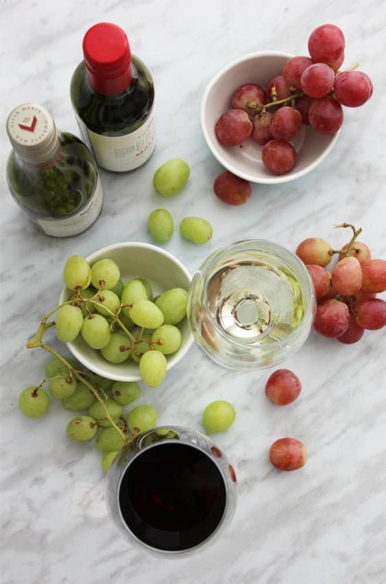 A top shot of two glasses of wine with grapes