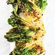 Top down shot of cooked pak choi halves with chili and garlic