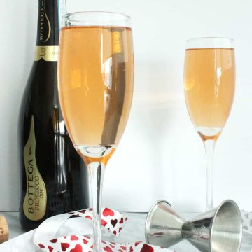 Two glasses of a prosecco brunch cocktail with a red ribbon