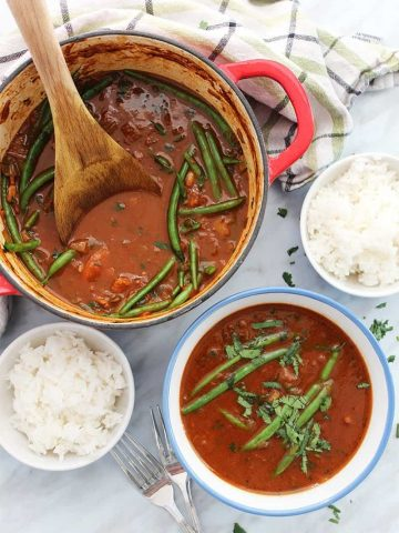 Beef curry stew in a large pot with wooden spoon