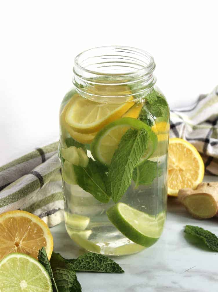 A mason jar of infused water with fresh lemon, lime and mint inside it