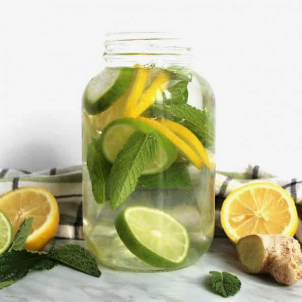 A jar of infused water next to the ingredients