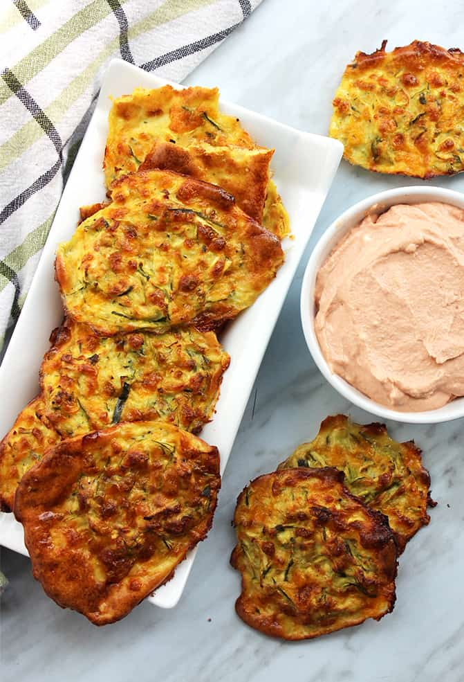 Top down shot of baked zucchini fritters on a white serving plate