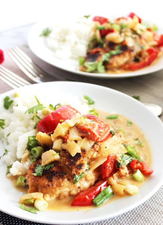 Chicken coconut Thai curry served on two white plates and garnished with fresh herbs
