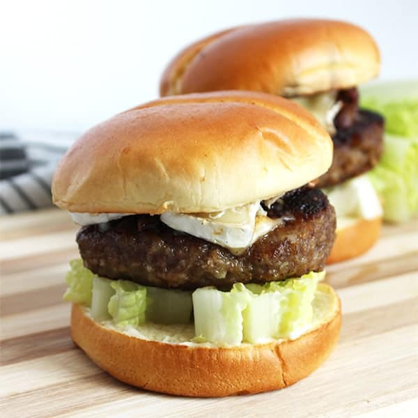 Two honey and truffle burgers on a wooden board