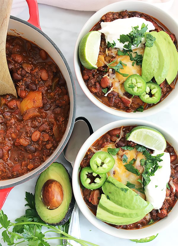 Two bowls of roasted ground beef chili topped with sour cream and avocado