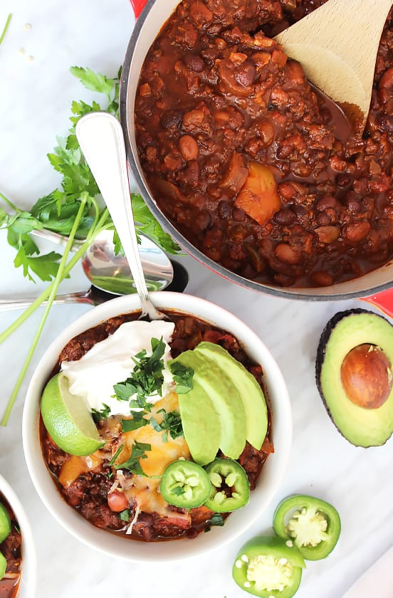 A bowl of roasted ground beef chili next to a pot of chili