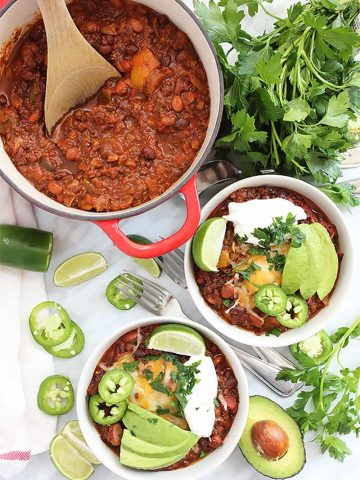 Two bowls of roasted ground beef chili and chili in a red pot