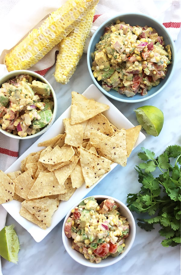 Three bowls of corn salsa with avocado served with tortilla chips
