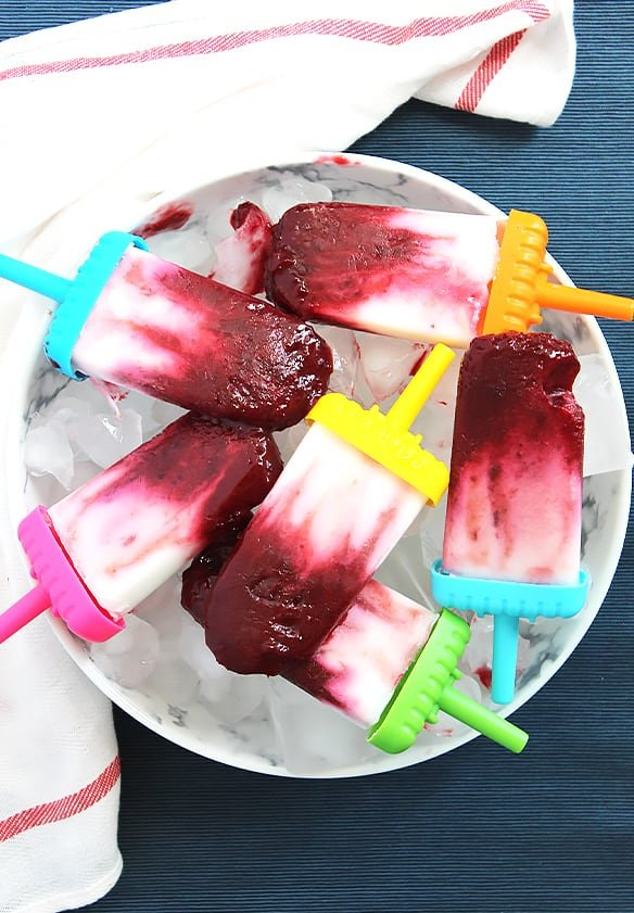 Six cherry and yogurt popsicles in a shallow bowl