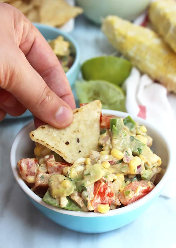 A tortilla chip scooping up some corn salsa