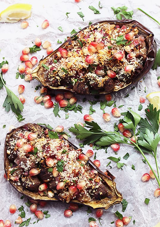 Two halves of stuffed eggplant on a white background