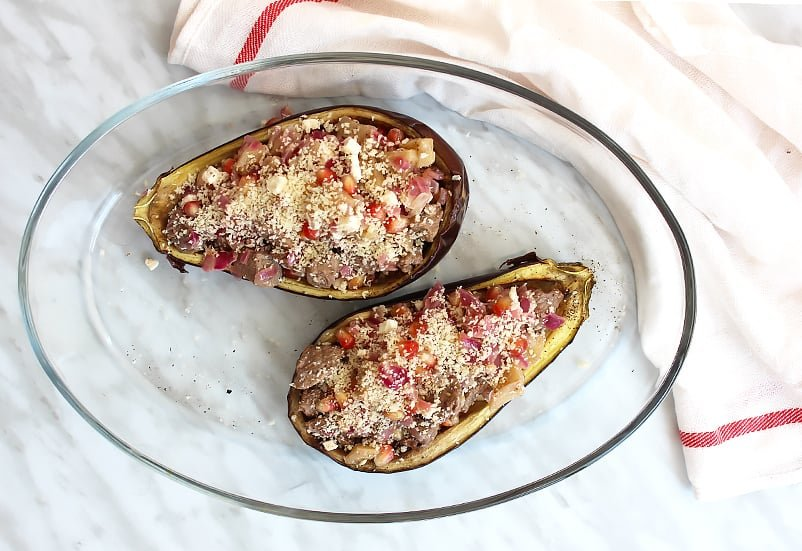 Two stuffed eggplant halves in a glass baking dish before being baked
