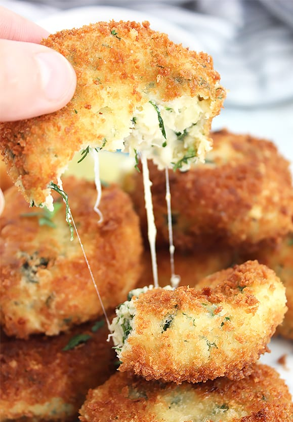 Pulling a crab cake apart to show the cheese strings