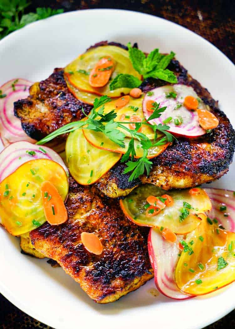 Turmeric pork chops served on a white plate