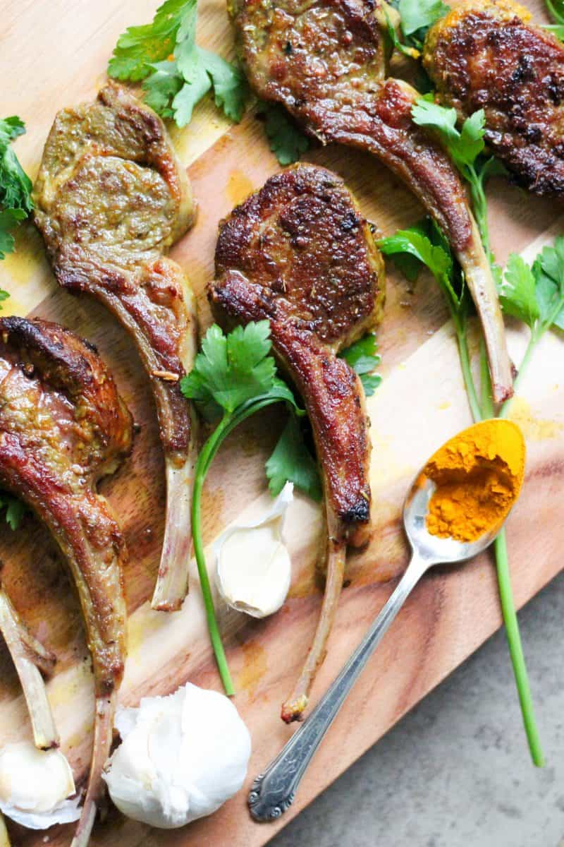 Turmeric lamb chops on a wooden chopping board