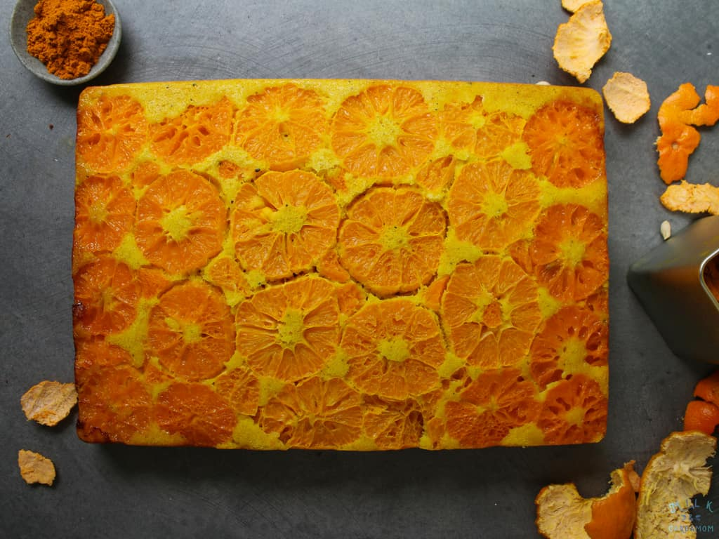 An orange and turmeric cake on a work surface