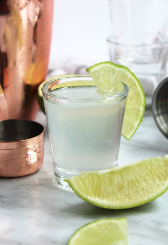 A shot with a slice of lime next to a lime wedge and cocktail shaker