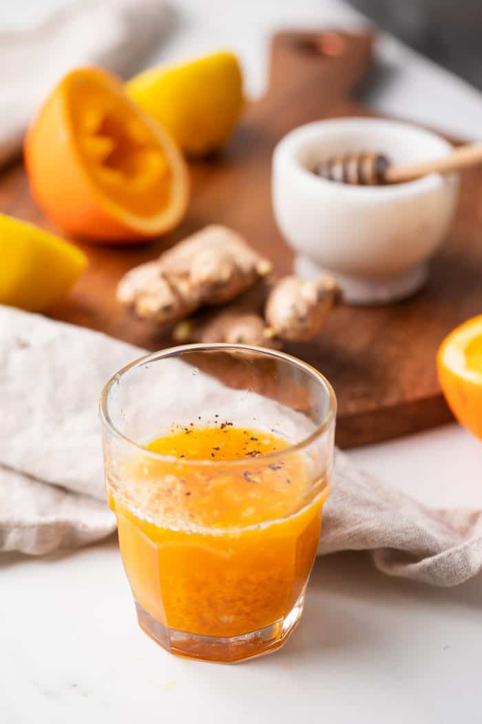 A turmeric shot in front of the ingredients to make it