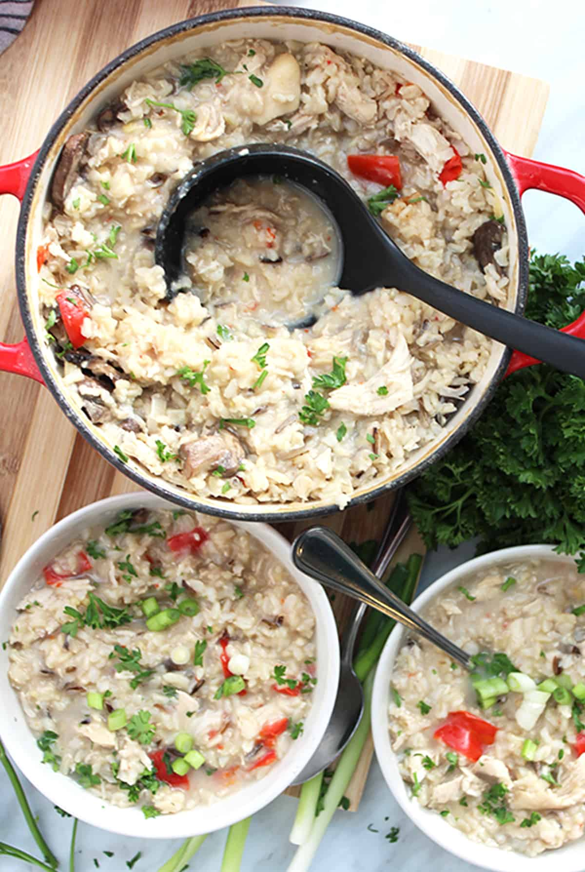 A ladel in a pot of the chicken and rice soup with two white bowls ready to eat