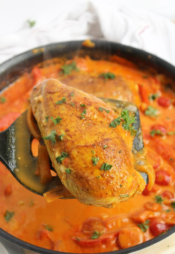 Lifting the cooked chicken breast out of the skillet on a spatula