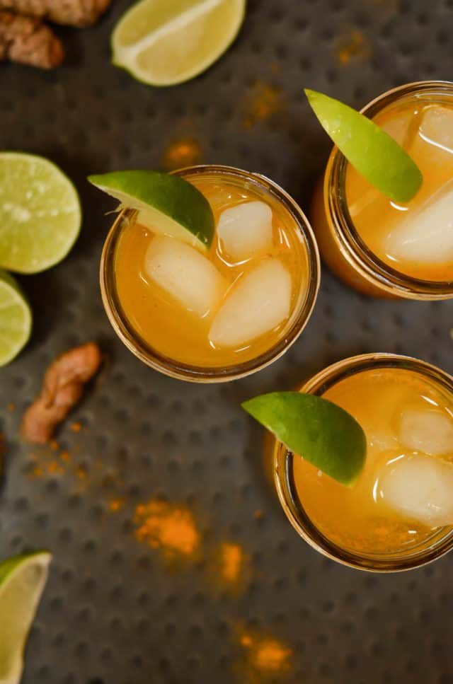 Two turmeric cocktails garnished with lime wedges