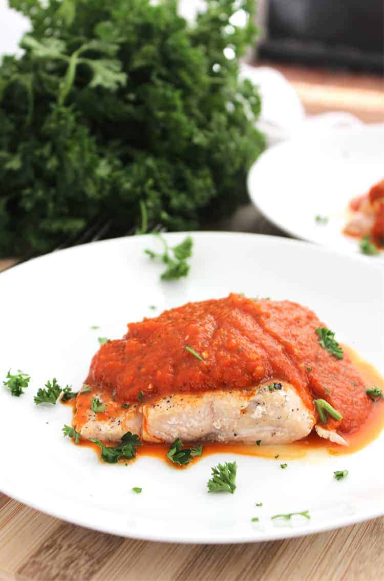 Baked salmon on a white plate topped with pepper sauce