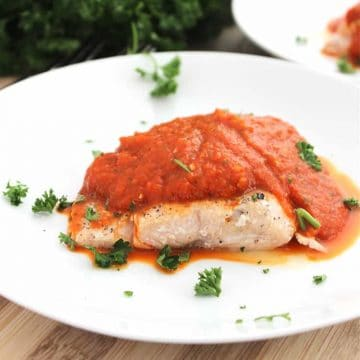 Salmon served with red pepper sauce on a white plate