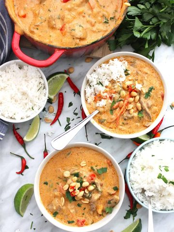 Two bowls of panang curry served from a dutch oven