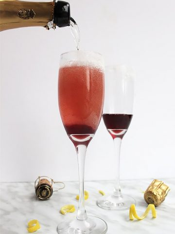Champagne being poured into a glass with cherry simple syrup