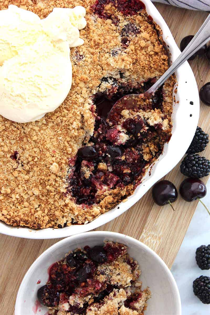 The baked crumble in a pie dish being served into a bowl with a spoon
