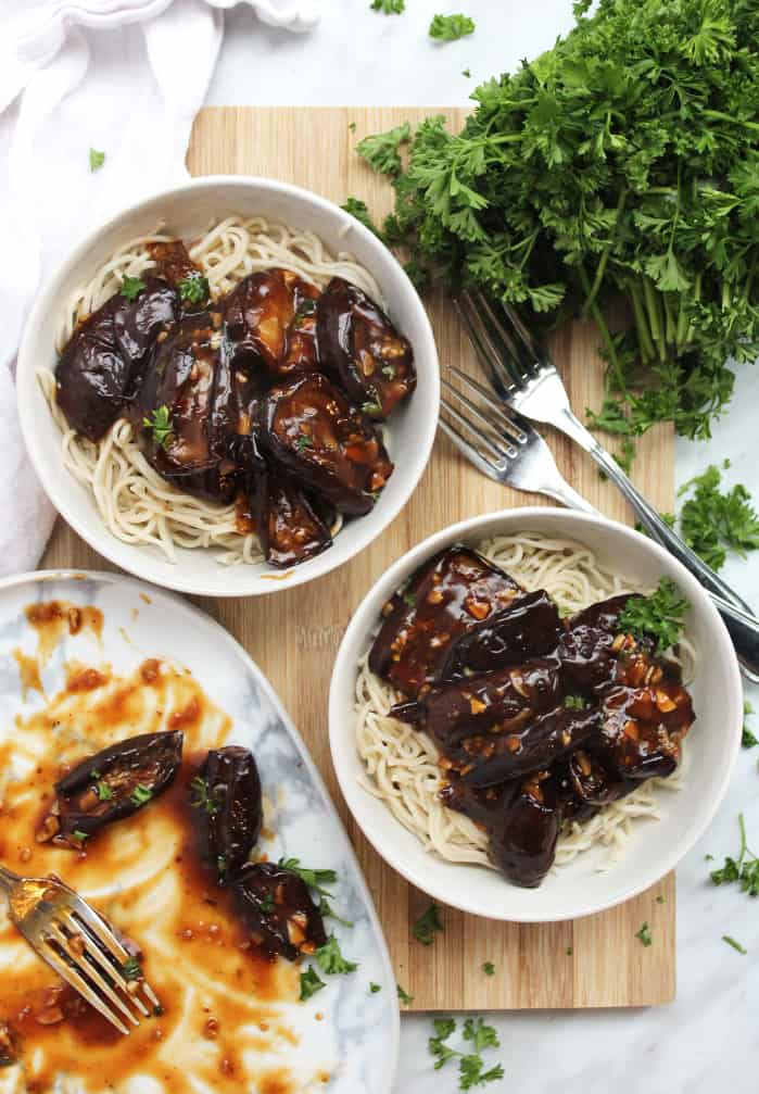 Roasted eggplant in two bowls on a wooden chopping board