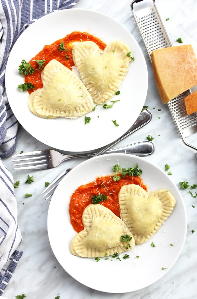 Two white plates with heart shaped ravioli and sauce