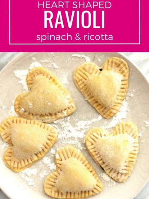Pinterest image. Heart shaped ravioli on a plate before cooking with text overlay