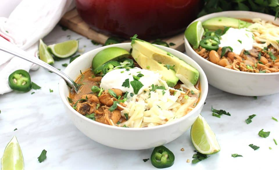 White bean chili served in two white bowls with fresh toppings