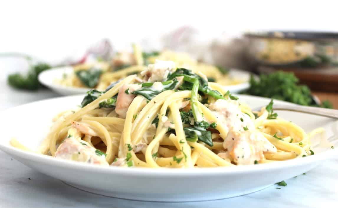 A side view of the lemon and salmon pasta on a white plate