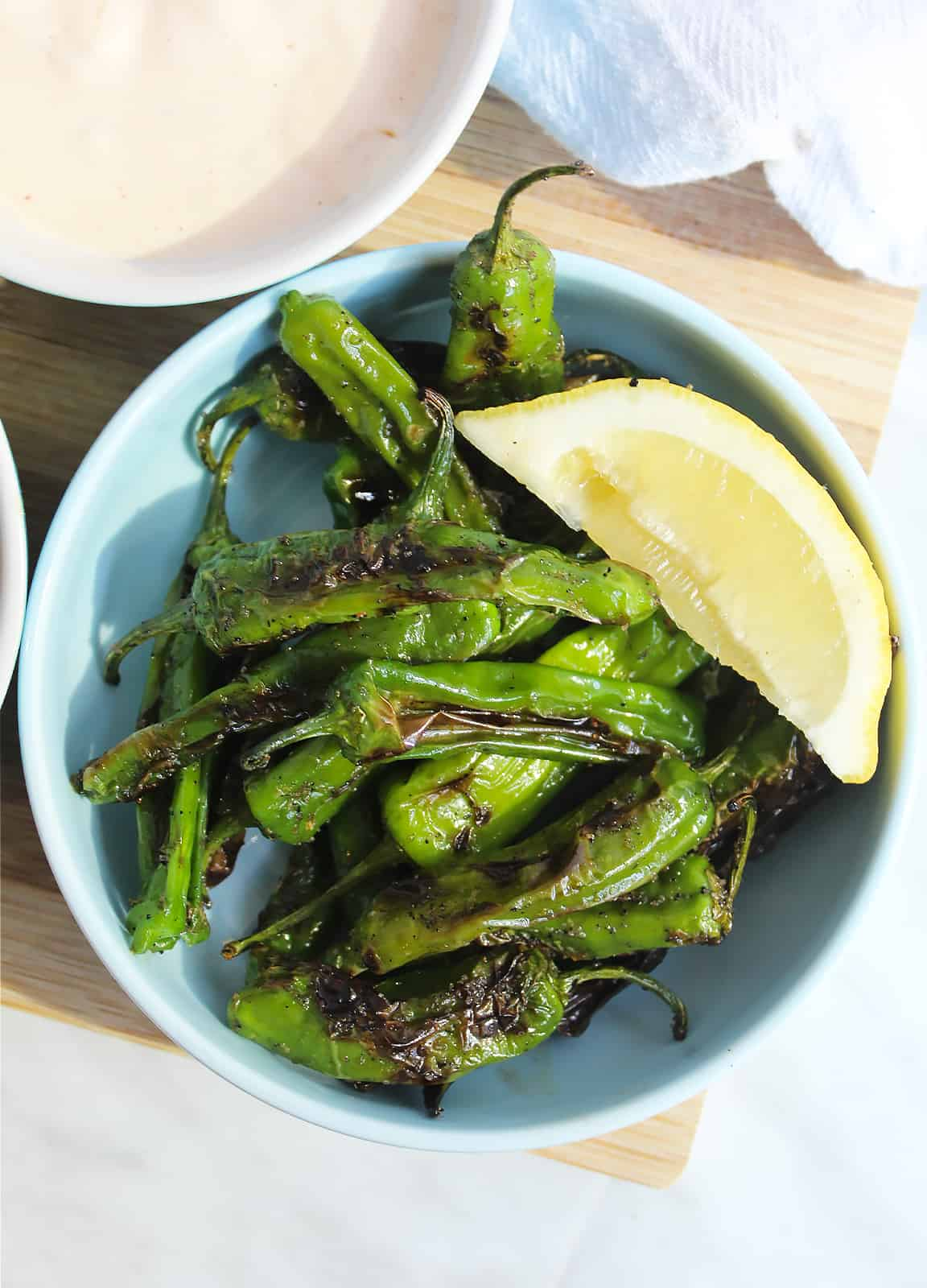 Shishito peppers in a bowl with a lemon wedge
