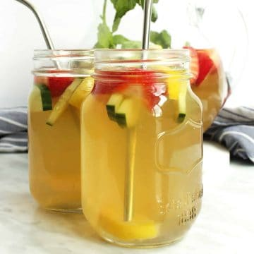 Two glasses of spiked iced green tea with straws