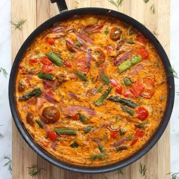 An oven baked frittata in a skillet garnished with herbs